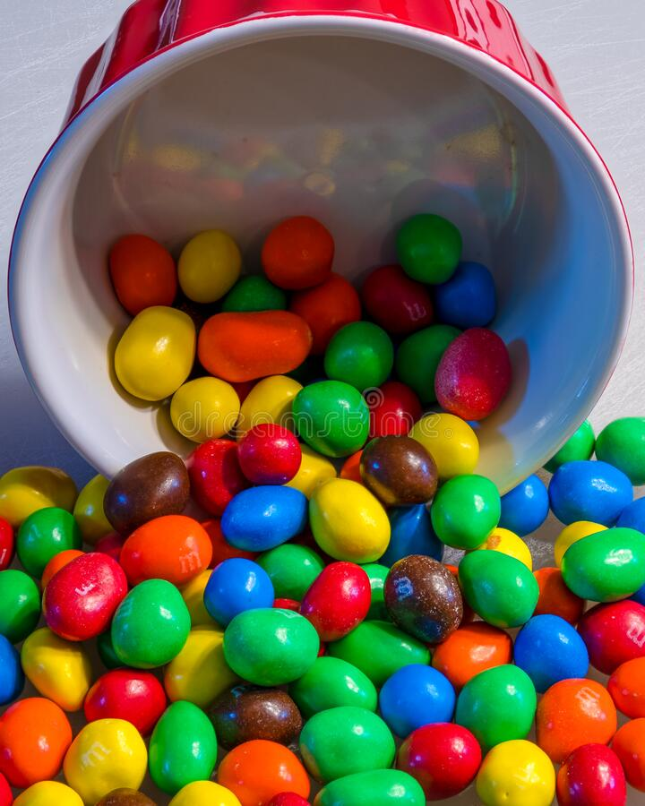 Peanut M&M`s spilling out of a red colorful bowl royalty free stock image