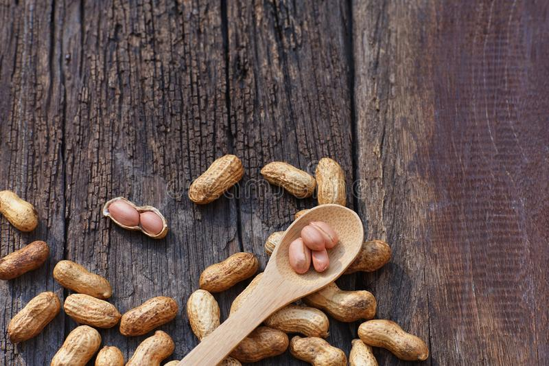 Peanut, snack, in wood spoon on classic wooden table background. Copy space brown ingredient arrangement group food almond hazelnut seed roasted walnut organic royalty free stock images