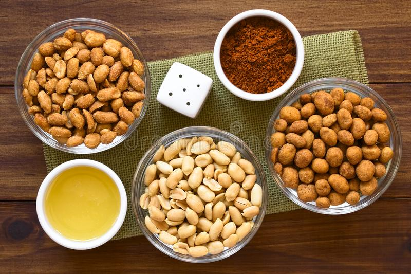 Peanut Snacks. In glass bowls. Peanuts with honey and salt, salted peanuts, peanuts roasted in a spicy coat. Photographed overhead on dark wood with natural royalty free stock photo