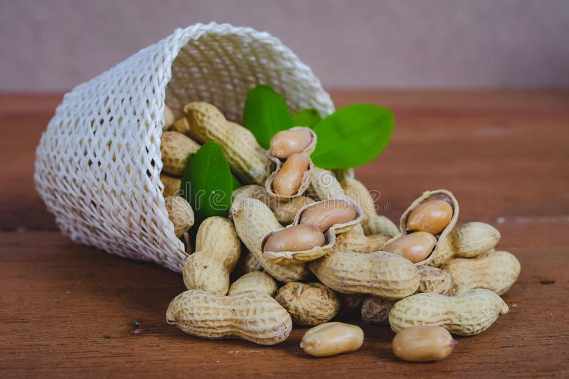 Peanut spill out of basket on wood royalty free stock photos