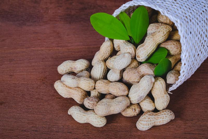 Peanut spill out of basket on wood royalty free stock photography