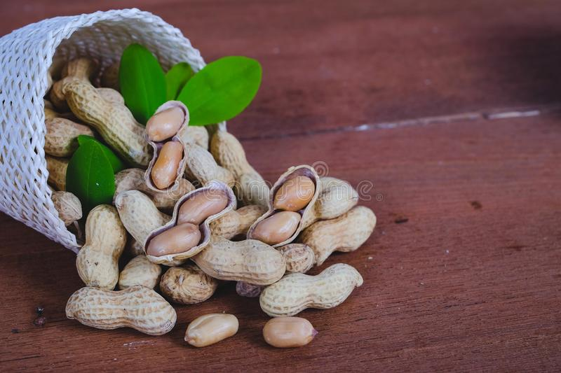 Peanut spill out of basket on wood. Background royalty free stock photos