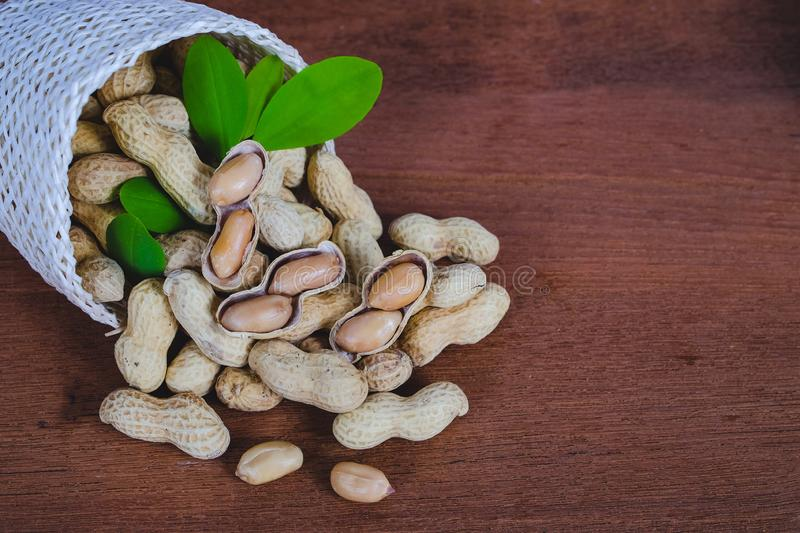 Peanut spill out of basket on wood royalty free stock image