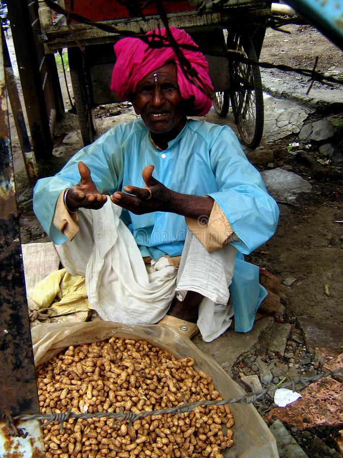 Peanut Vendor. An old Indian sells peanuts for living royalty free stock photography