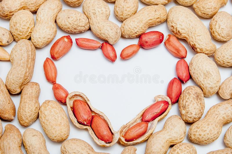Peanuts, for background or textures. Uncleaned inshell peanuts. Peanuts isolated on white background. Valentine`s Day, Flat lay. Copy space royalty free stock photography