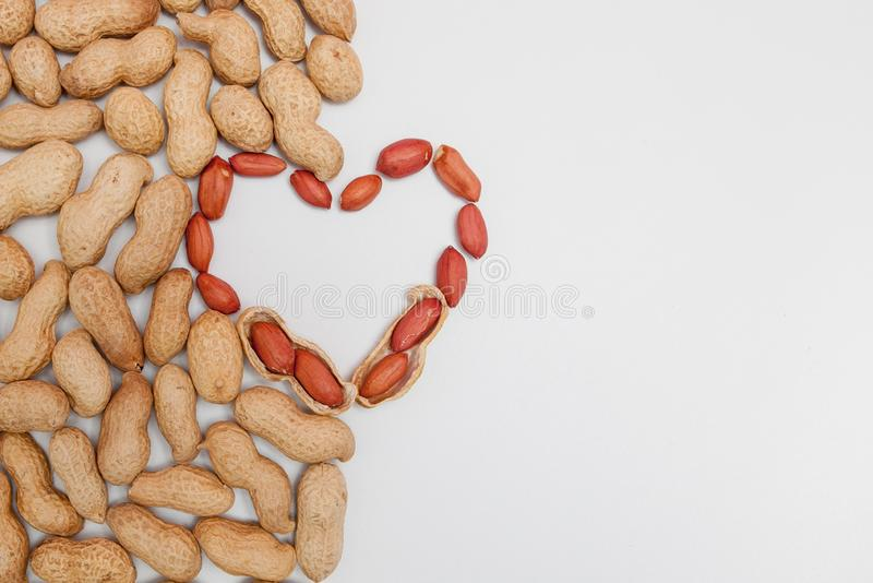 Peanuts, for background or textures. Uncleaned inshell peanuts. Peanuts isolated on white background. Valentine`s Day, Flat lay. Copy space stock image
