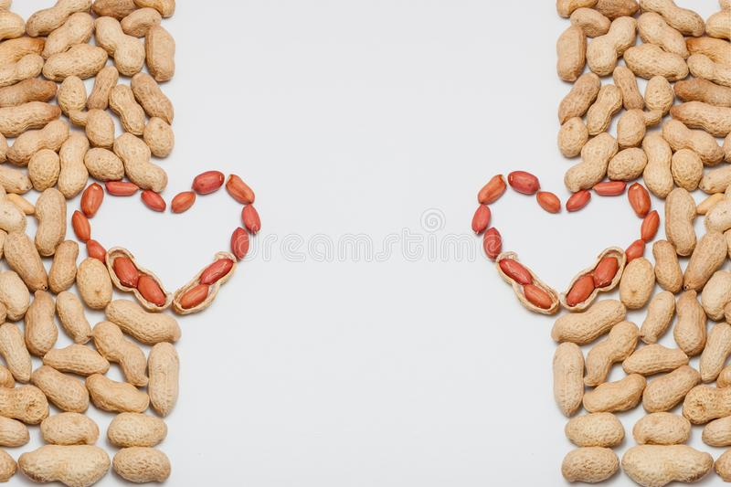 Peanuts, for background or textures. Uncleaned inshell peanuts. Peanuts isolated on white background. Valentine`s Day, Flat lay. Copy space stock photos