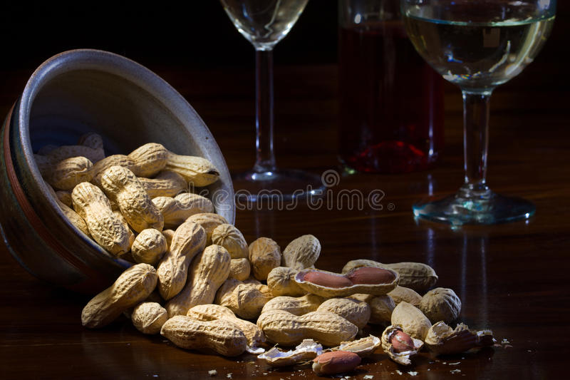 Peanuts in a ceramic bowl and on a dark wooden table, wine glass. Es in the background, evening scene at home royalty free stock images