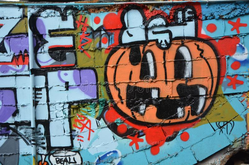 Snoopy and pumpkin graffiti in Portland, Oregon. This is the `Peanuts` character Snoopy on a Halloween pumpkin on a wall of the skateboard park underneath the royalty free stock photography
