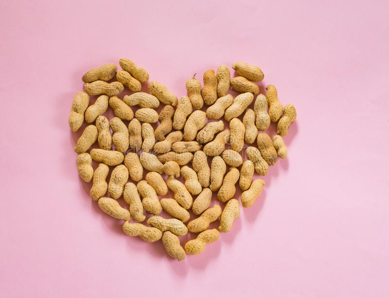 Peanuts forming a heart. On pink background royalty free stock photos