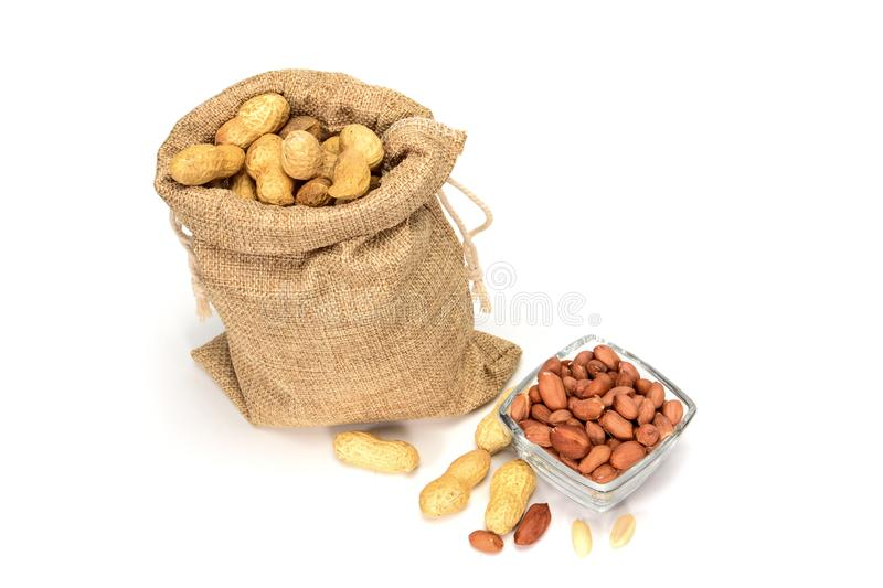 Peanuts. Jute burlap sack full of peanuts and glass bowl with peeled kernels,  on white background with shadows. royalty free stock photos