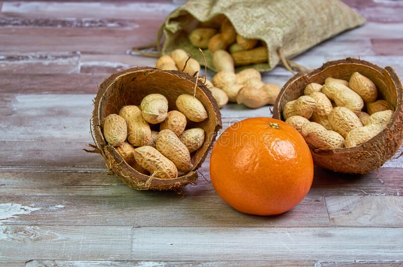 Peanuts lies in a coconut shell on a wooden table with orange tangerine fruit, healthy food, raw food stock image