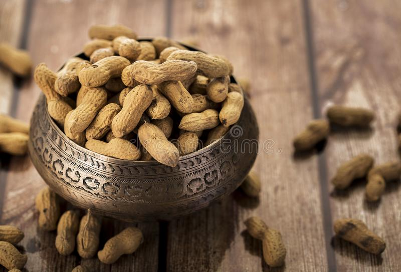 Peanuts in a metal bowl stock image