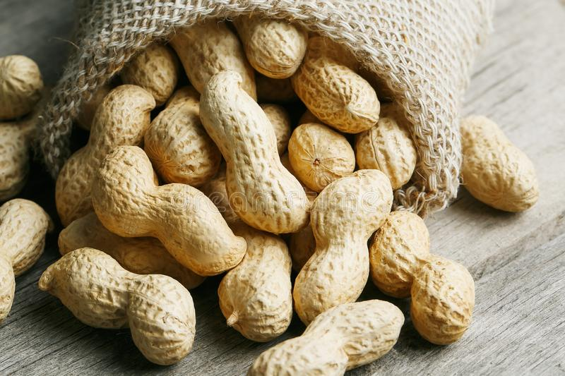 Peanuts in a miniature burlap bag on old, gray wooden surface royalty free stock images