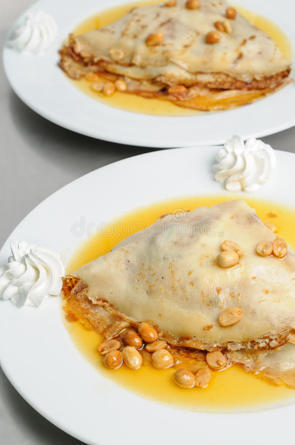 Peanuts pancake crepe dessert. Pancake crepe with peanuts and honey decorated with whipped cream stock photography