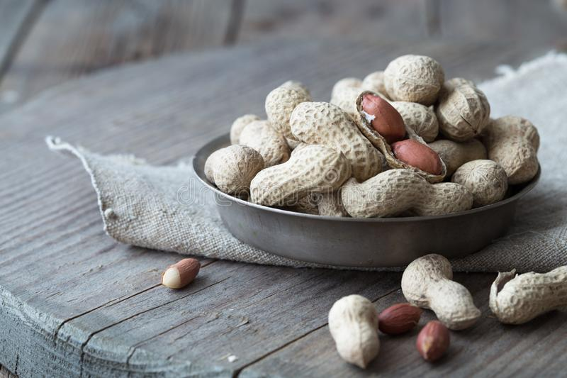 Peanuts in the shell and peeled close up in a cup. Background with peanuts. Roasted peanuts in the shell and peeled on a backgroun stock photos