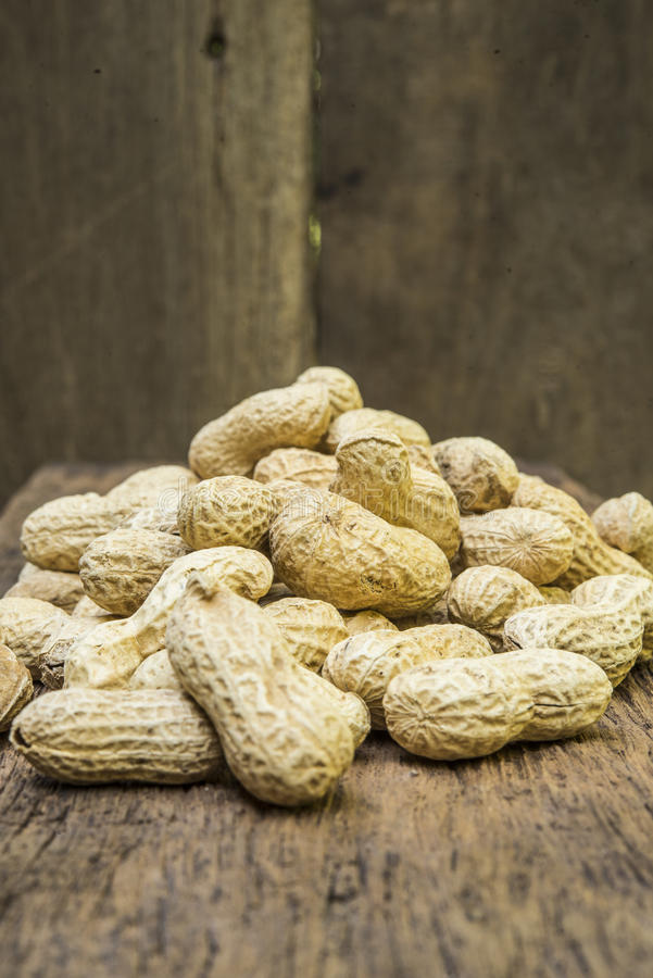 Peanuts in shells on wood background stock photography