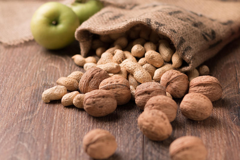 Peanuts, walnuts,green apples on a wooden background stock photo