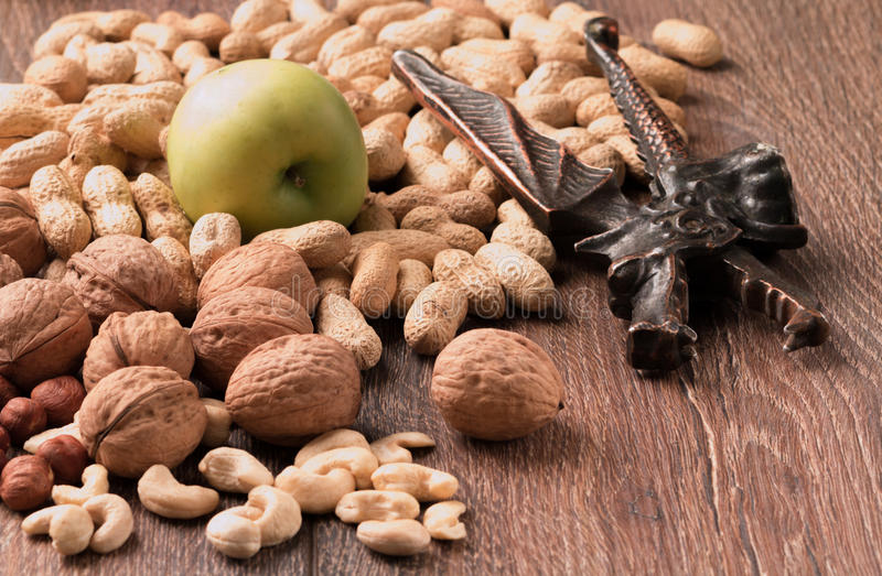 Peanuts, walnuts on a wooden background, nutcracker, green apples royalty free stock photography