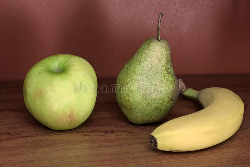 Pear, apple and banana on wooden background royalty free stock photos