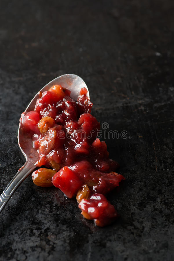 Pear cranberry relish. In spoon over dark background, copy space, selective focus stock images