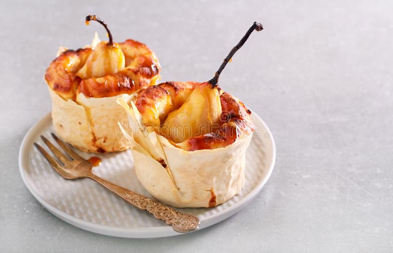 Pear mini cake with caramel sauce. On plate stock photography