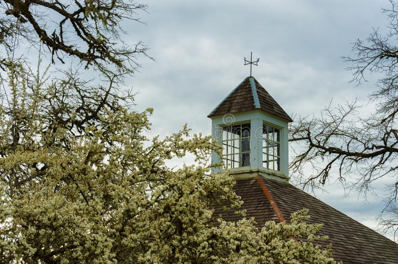 Pear tree blossom frame the roof top of a carriage house royalty free stock photography