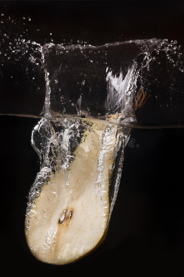 Pear in the water. Pear dropped into the water royalty free stock photography