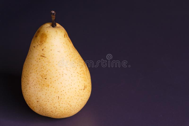 Pear williams. Whole yellow pear williams on purple background royalty free stock photography