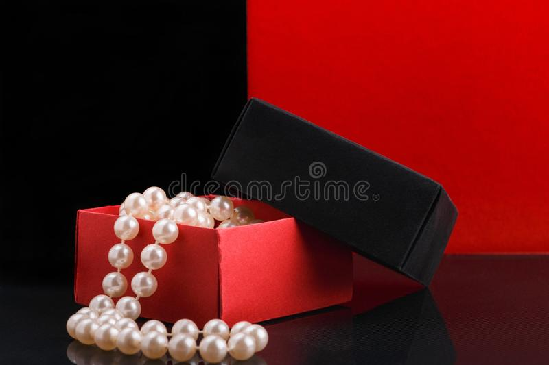 Pearl beads in opened homemade paper gift box on glossy surface. Pearl beads in opened homemade black and red paper gift box on glossy surface stock photos