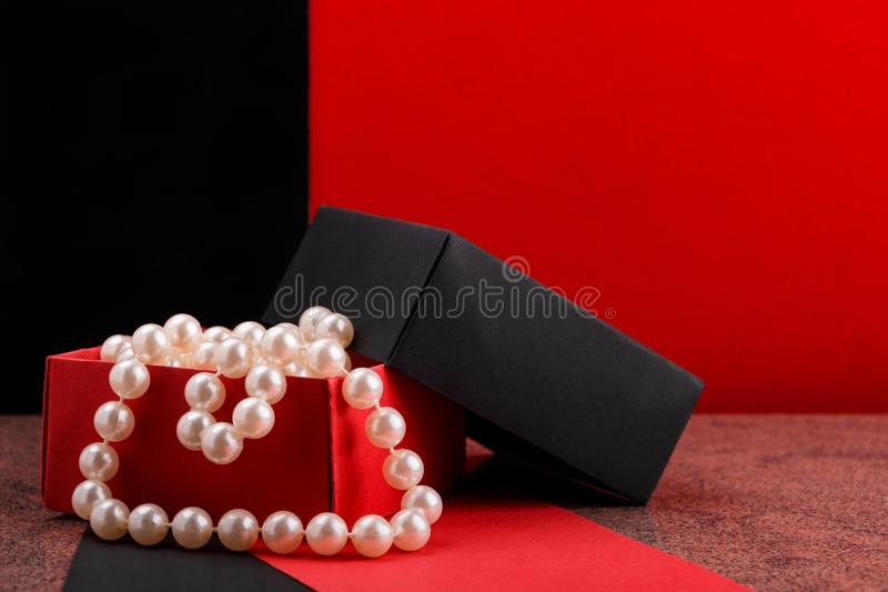Pearl beads in opened homemade paper gift box on granite surface. Pearl beads in opened homemade black and red paper gift box on granite surface royalty free stock photo