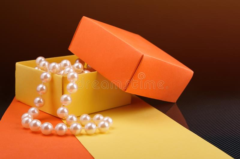 Pearl beads in opened homemade paper gift box on dark background. Toned light. Pearl beads in opened homemade yellow and orange paper gift box on dark background royalty free stock image