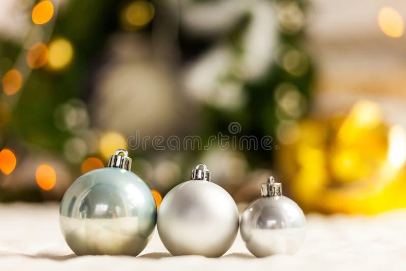 Three Pearl Christmas balls with colorful bokeh stock photography