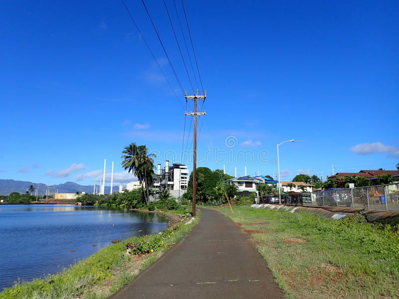 Pearl Harbor Bike Path. Along the water with Power lines overhead leading to power plant in the distance on Oahu, Hawaii royalty free stock photography