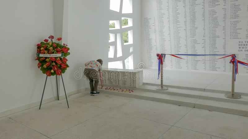 PEARL HARBOR, UNITED STATES OF AMERICA - JANUARY 12 2015: a visitor lays a wreath at the uss arizona memorial at pearl harbor. In hawaii stock photography