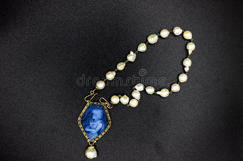 Pearl necklace with blue coral pendant also called cameo, depicting a stately woman. Naples Italy. Pearl necklace with blue coral pendant also called cameo stock images