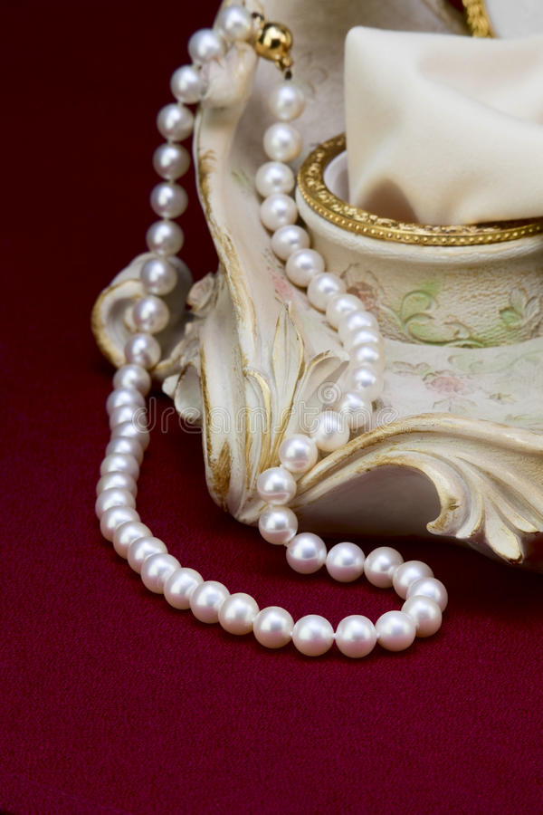 Pearl necklace. Beside the ceramic jewelry box on red background stock photos