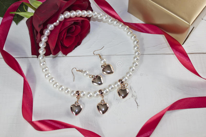 Pearl necklace with earring with golden hearts on white wood. Pearl necklace with earring with golden hearts, red rose, red ribbon and golden gift on white wood stock images