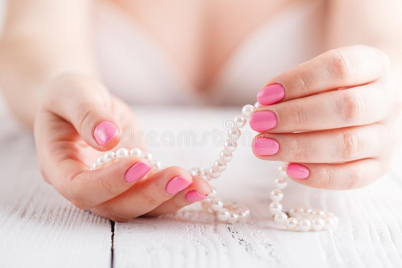 Pearl necklace in female hands, close up view royalty free stock images