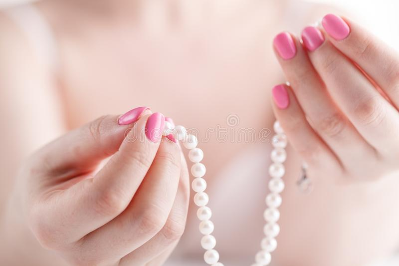 Pearl necklace in female hands, close up view stock image
