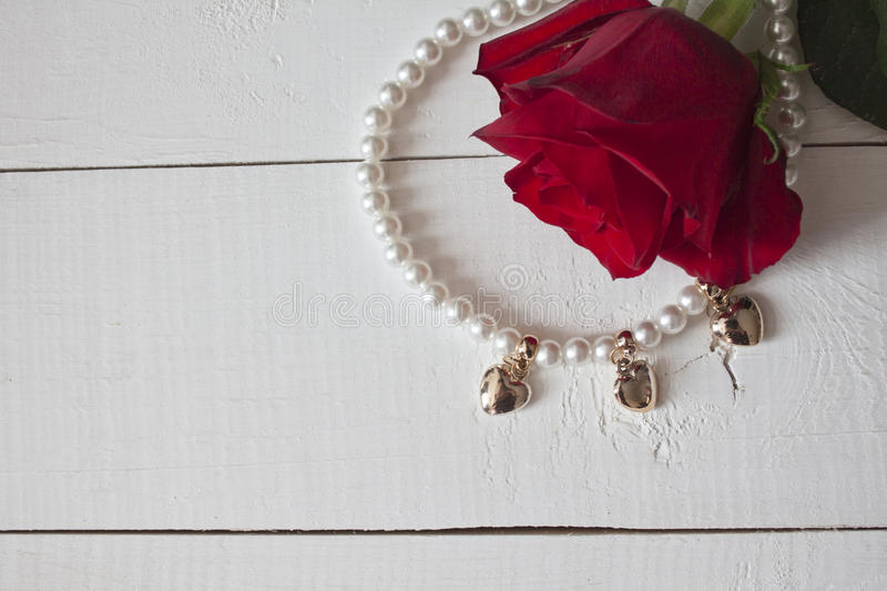 Pearl necklace with golden hearts on white wood. Pearl necklace with golden hearts and red rose on white wood royalty free stock photo