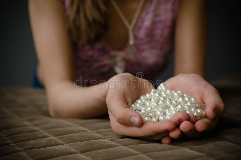 Pearl necklace in hand girl royalty free stock images