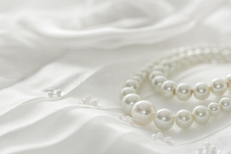 Pearl necklace on lace background. stock photos