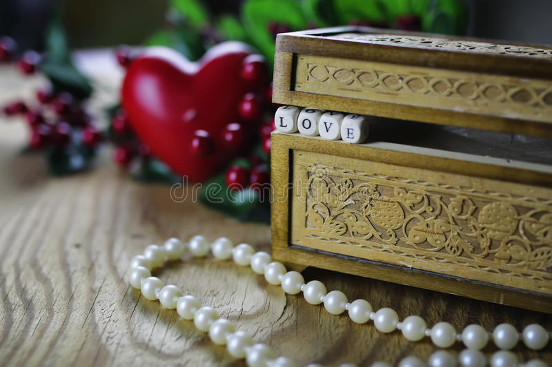 Pearl necklace love box. Jewelry items on a wooden table in the texture of patterned wooden box stock images