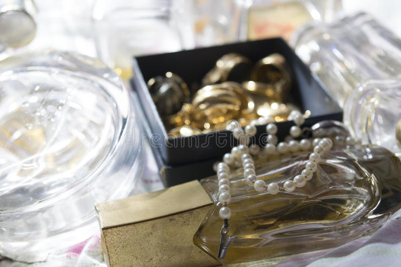 Pearl necklace on perfume bottle and family jewels royalty free stock photo