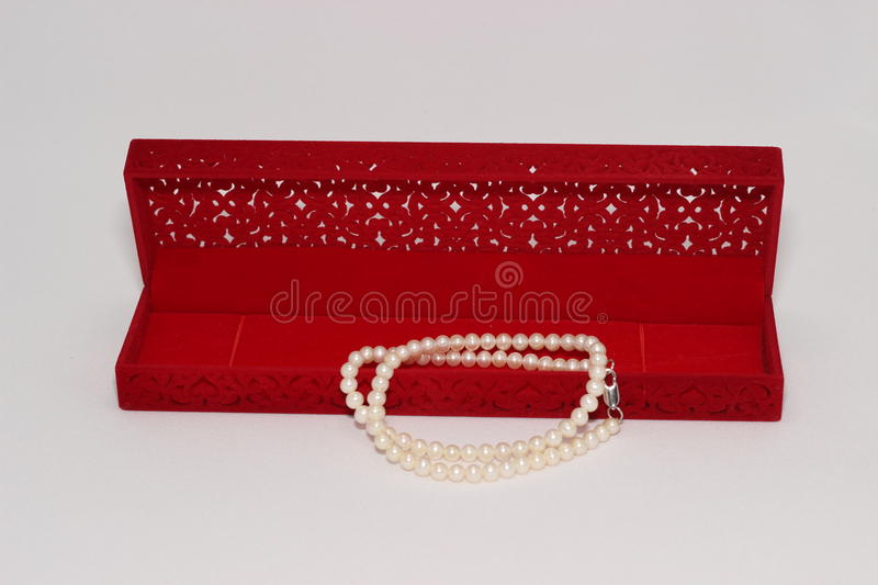 Pearl necklace and red gift box royalty free stock image