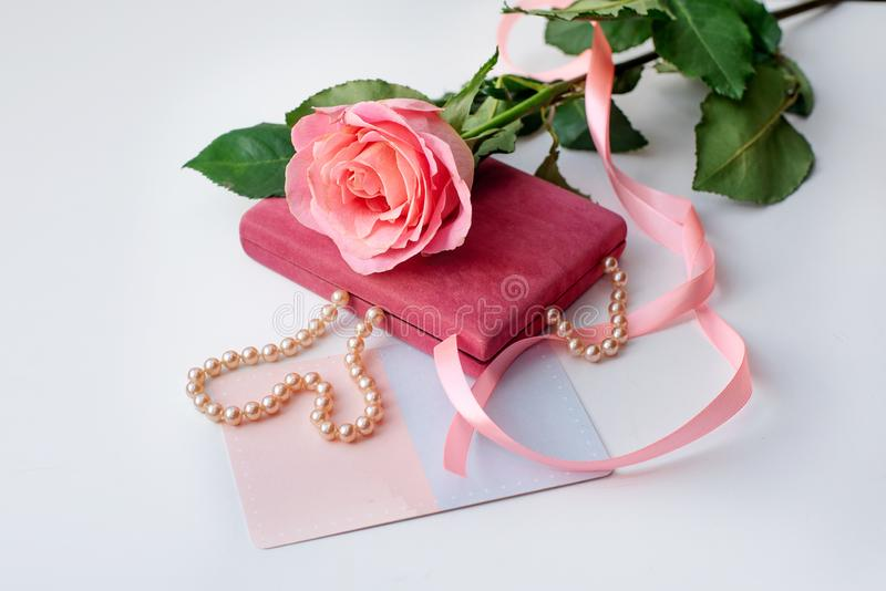 Pearl necklace on rose velvet box and pink one rose with gift card. Light background stock photos
