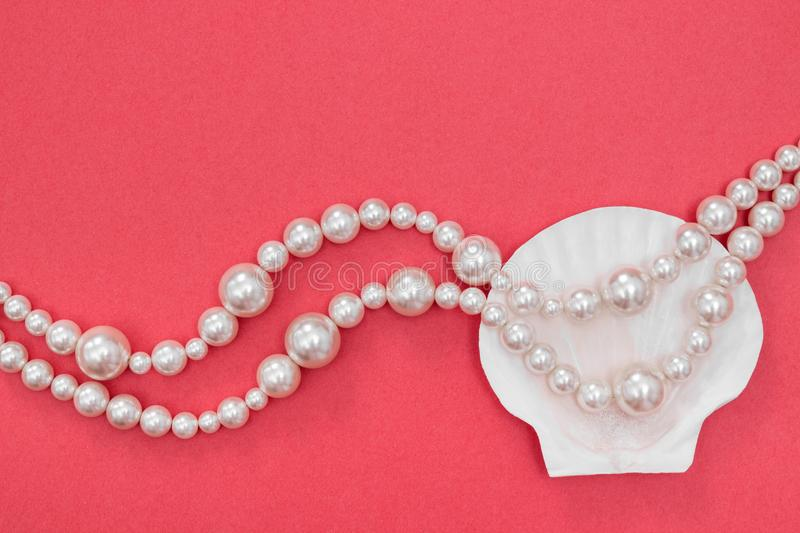 Pearl necklace and seashell on pink background. Pearl necklace and seashell on vibrant pink background. Fashion concept royalty free stock images