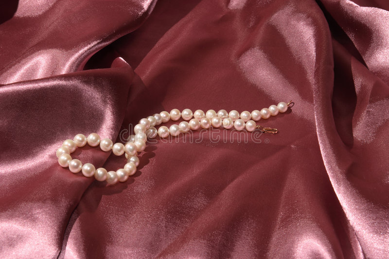 Pearl necklace for you. White pearl necklace on dark pink satin royalty free stock photos