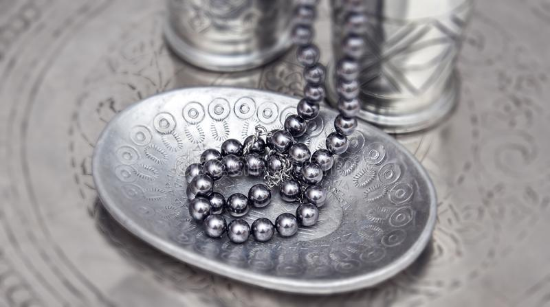 Pearl necklet on a silver plate royalty free stock images